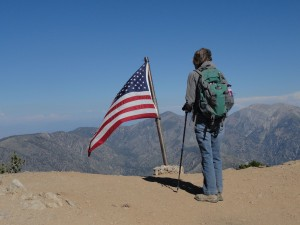 Joanie Kasten stands at Mt. Baden-Powell's summit.  Pine Mountain and Mt. Baldy make up the backdrop as Old Glory flies in a brisk mid-summer breeze.